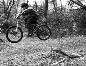 Boy performs jump on push bike in woods